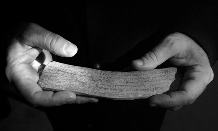 Driftwood tablet with engraved property texts and testaments preserved in fortified attics in Morocco. Rachid Koraïchi's hands